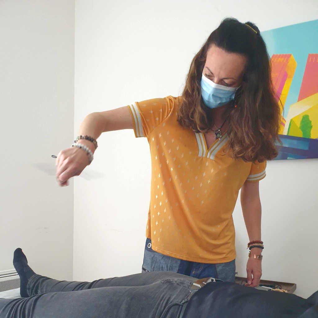 Dans le cadre de la formation magnétisme et thérapeute holistique, une élève rééquilibre les chakras au pendule